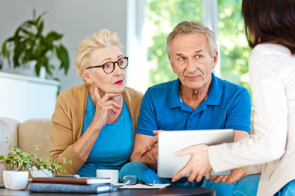 Elderly couple discussing with financial advisor at home