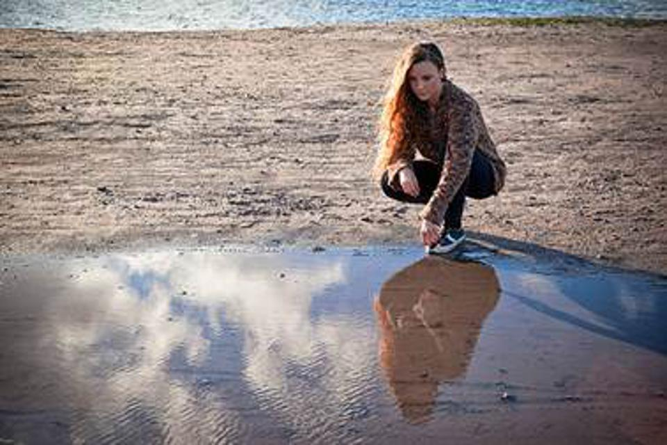 A woman looks at her reflection in a puddle