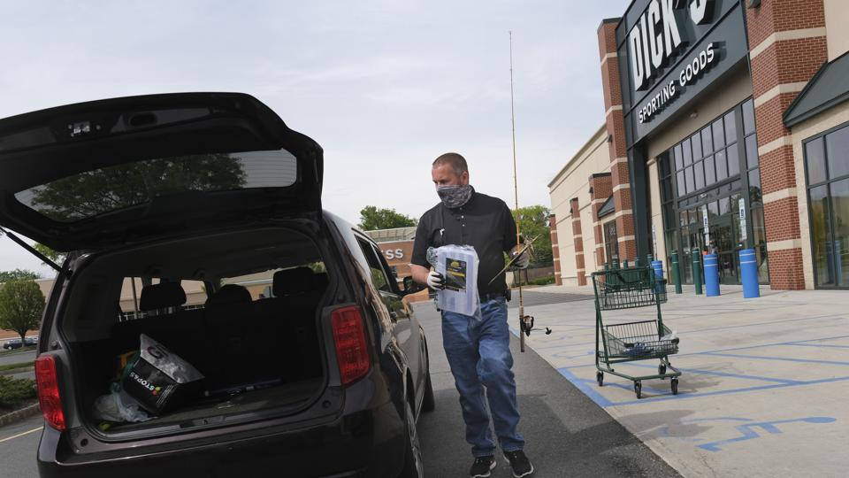 A worker at Dick's Sporting Goods in Paramus, N.J. delivers a curbside pickup order to a customer waiting in their SUV, with the hatchback door open.