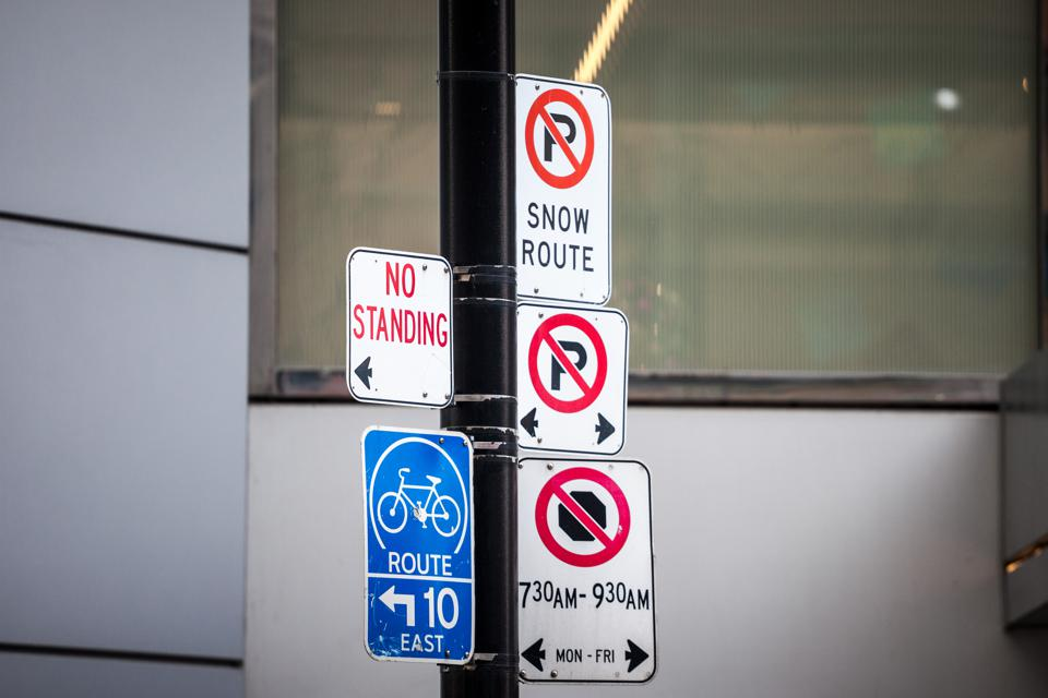 North American no parking signs and a roadsign indicating a bike lane abiding by North American standard in Toronto, Canada. The city is  developing bicycle as an ecological transportation alternative