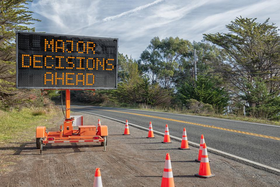 DECISIONS AHEAD: Roadside sign: Trailer mobile warning sign parked by road with words for safety by orange cones