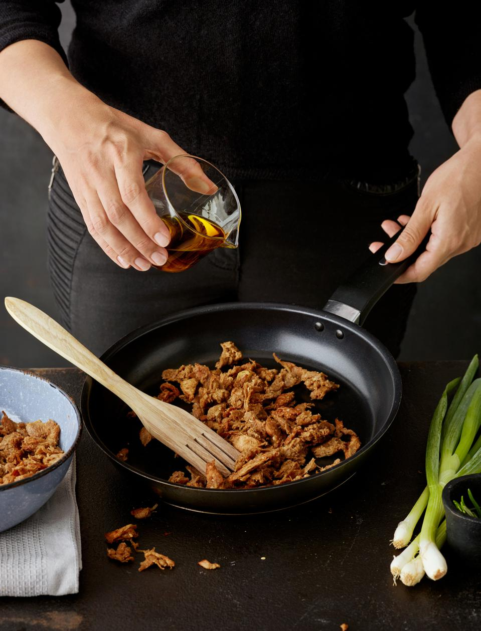 Someone pouring oil into a skillet with Pulled Oats meat alternative next to a bunch of green onions