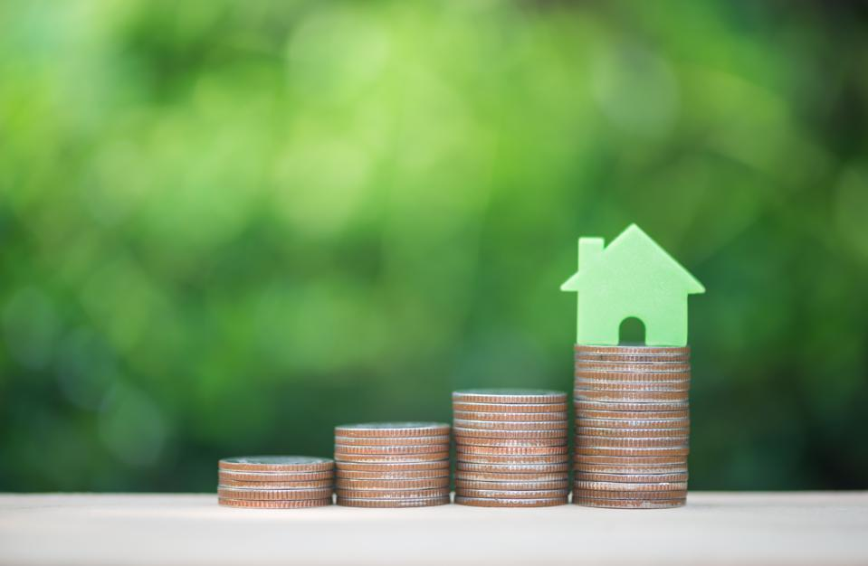 Home model on the growing coin stack for concept of money saving for home buying fund
