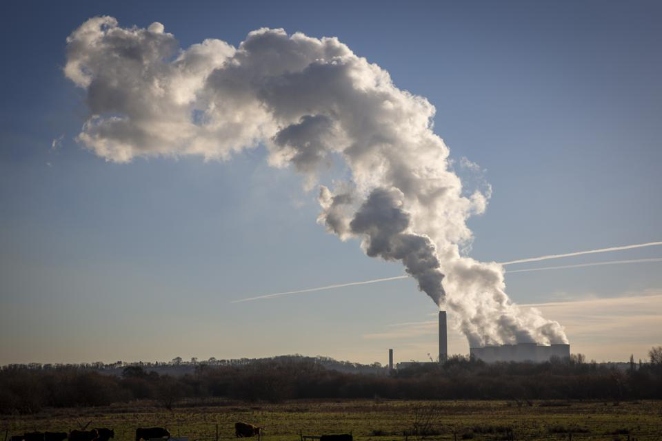 A coal fired power station emits a cloud of smoke and steam into a blue sky.