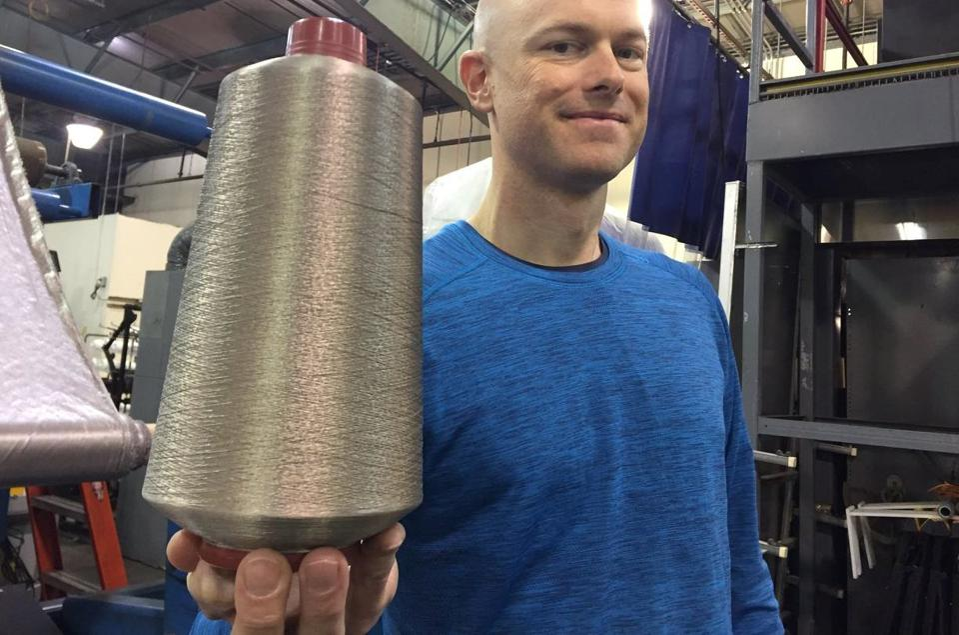 Noble Biomaterials cofounder Joel Furey holding a cone of silver yarn.