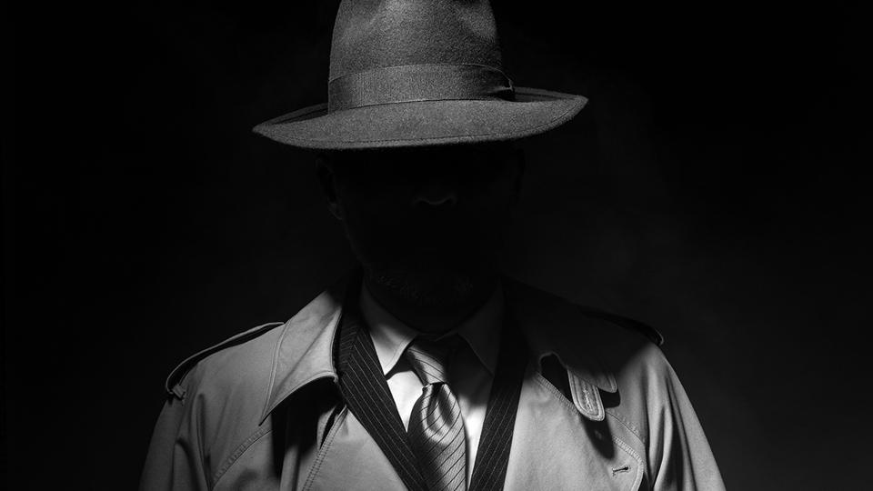 Man in a fedora hat and raincoat peers out of the dark, but his face is hidden in shadow.