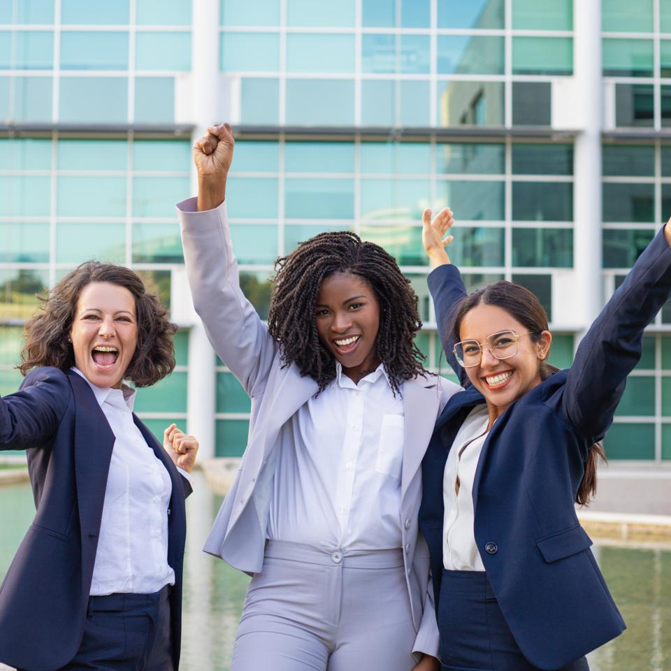 Happy excited businesswomen rejoicing at corporate success