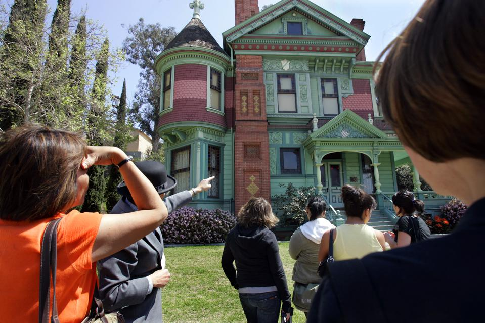 Photo of tour guide Mike Schutz points out the James and Bessie Hale house as part of the postcard