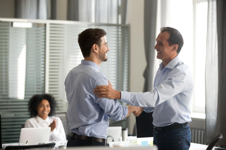 Smiling middle-aged ceo handshaking successful male worker showing respect