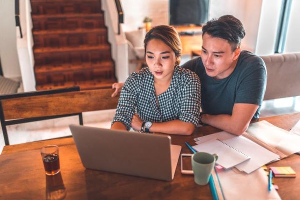 man and woman looking at laptop computer