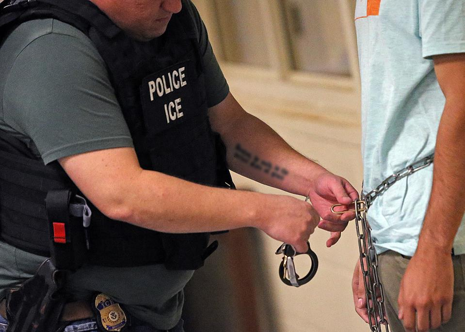 BURLINGTON MA. - SEPTEMBER 25: A ICE agent processes a man after being arrested for staying here in the United States illegally and having a criminal backgrounds on September 25, 2019 in Burlington, Massachusetts.  (Staff Photo By Matt Stone/MediaNews Gro
