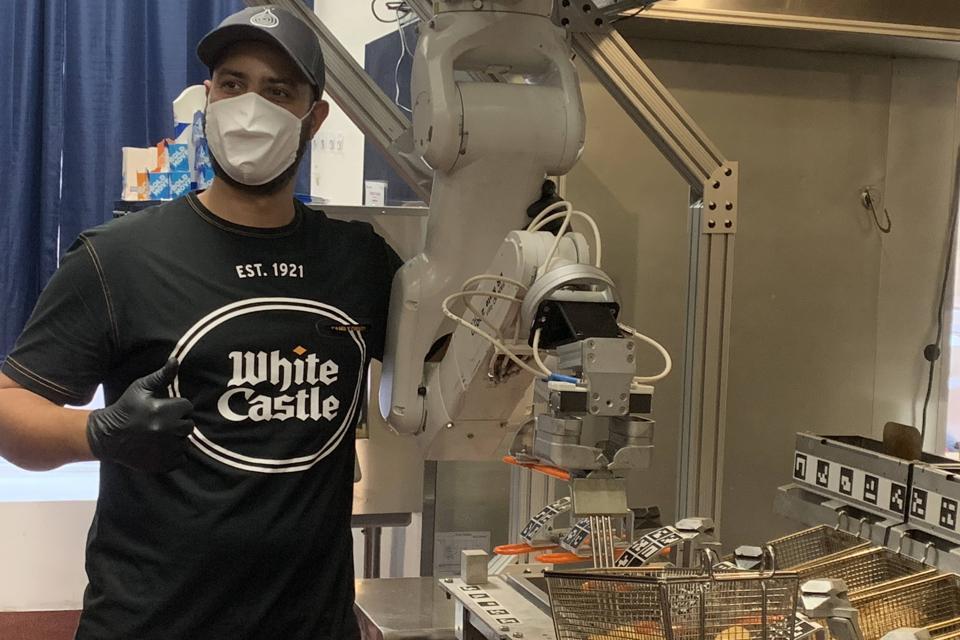White Castle team member standing next to Flippy.
