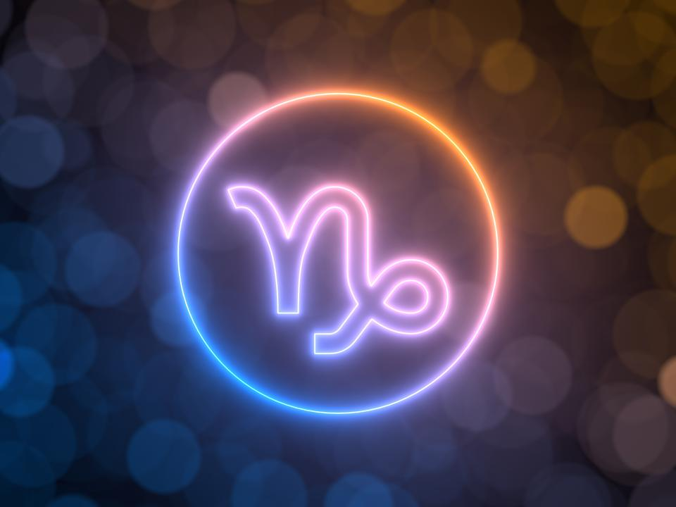 glowing neon sign of Capricorn with blurred bokeh background. 3d illustration