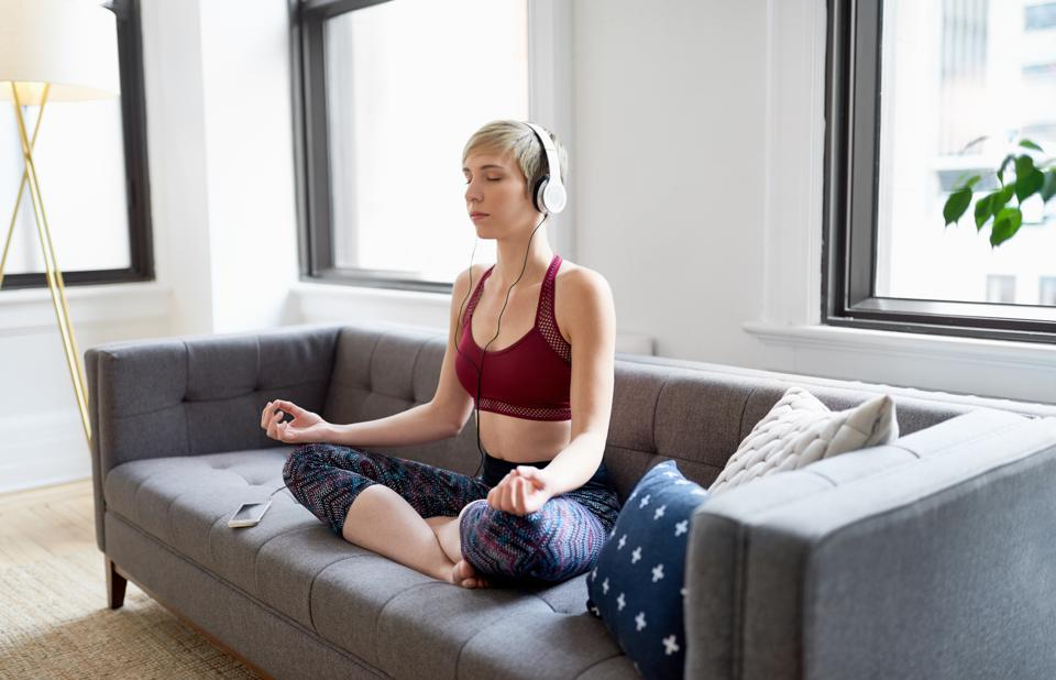 Trendy woman listening to a meditaion app as part of her mindfulness morning routine