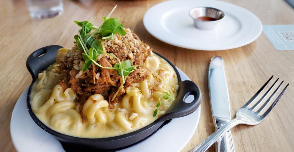Smoked pulled pork mac and cheese in a skillet with silverware and hot sauce