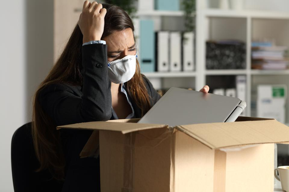 Fired executive with mask packing belongings at night