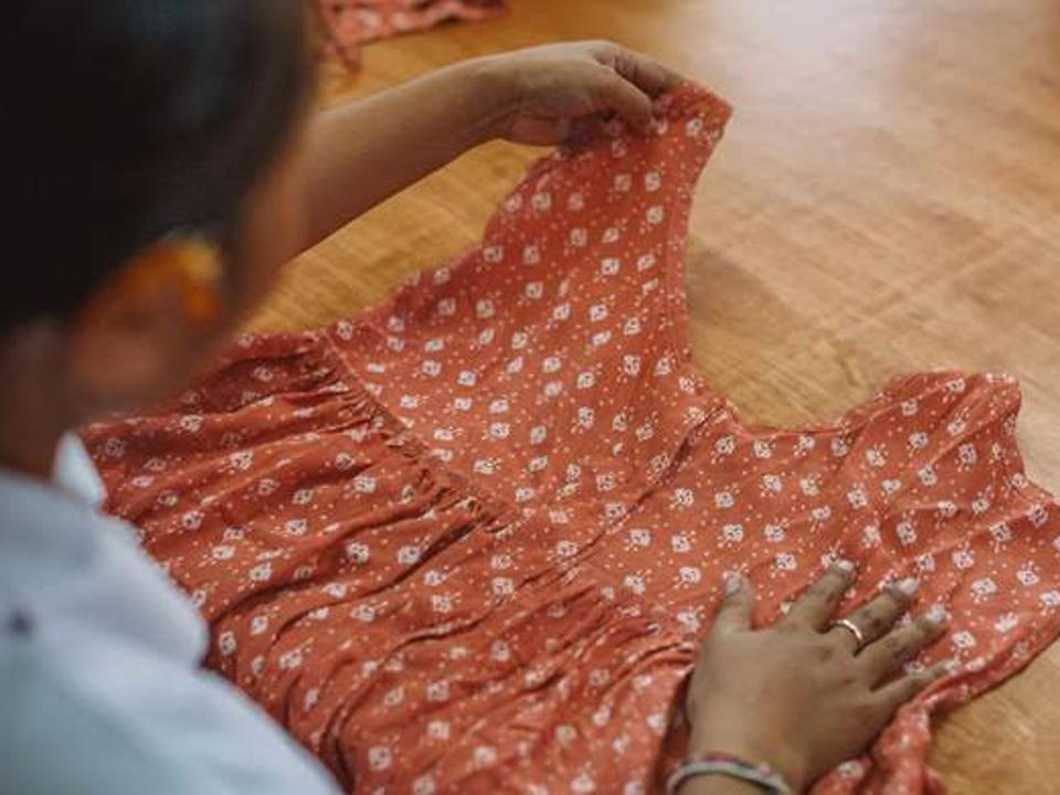 A woman examines an orange dress laid out on a desk
