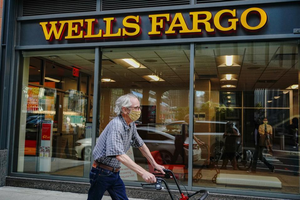 An elderly man wearing a face mask passes by a Wells Fargo...