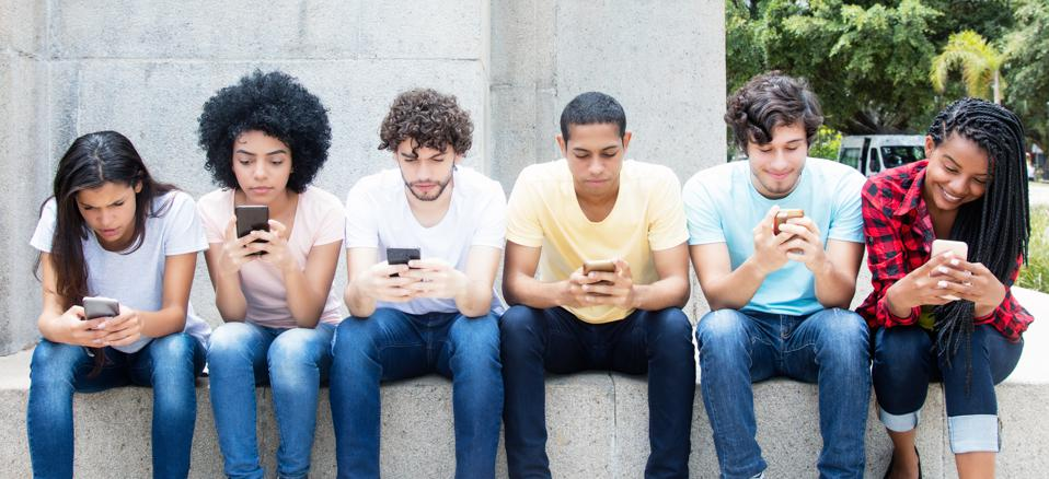 Group of young adults playing online game with phone