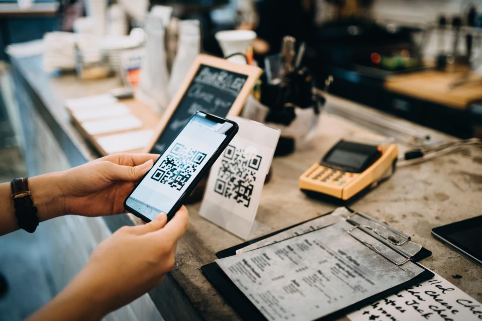 Customer scanning QR code, making a quick and easy contactless payment with her smartphone in a cafe