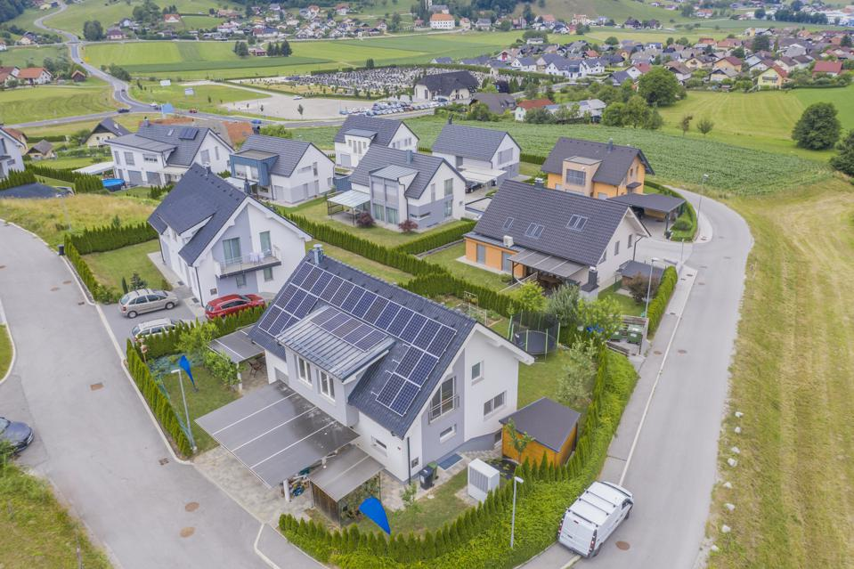 Aerial view of housing estate, the foremost house with solar panels on the roof.