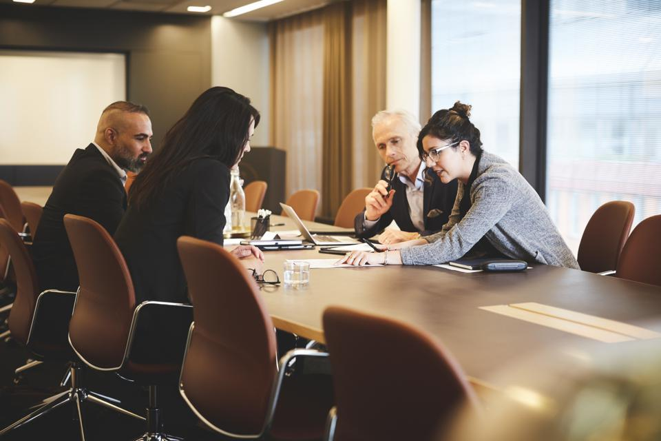 Male and female lawyers discussing over document at conference table in meeting