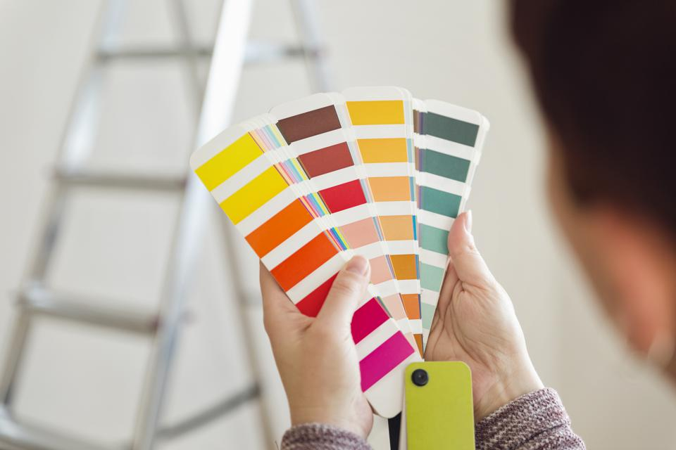 Woman holding colour sample in an empty room with a ladder