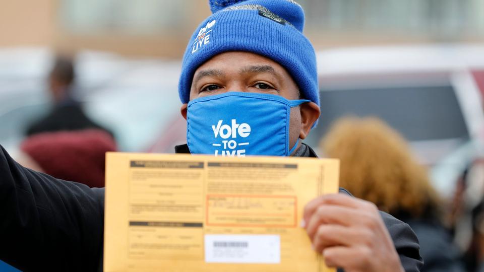 Biden rally supporter Detroit holds mail-in ballot