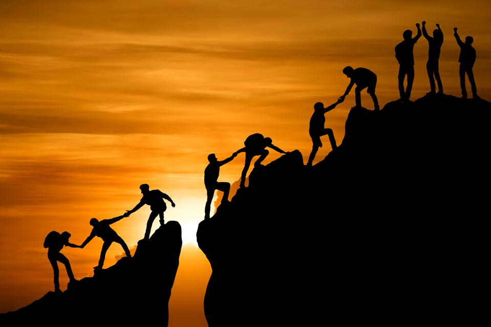 Group of People on the Peak of a Mountain Using Teamwork to Reach the Top