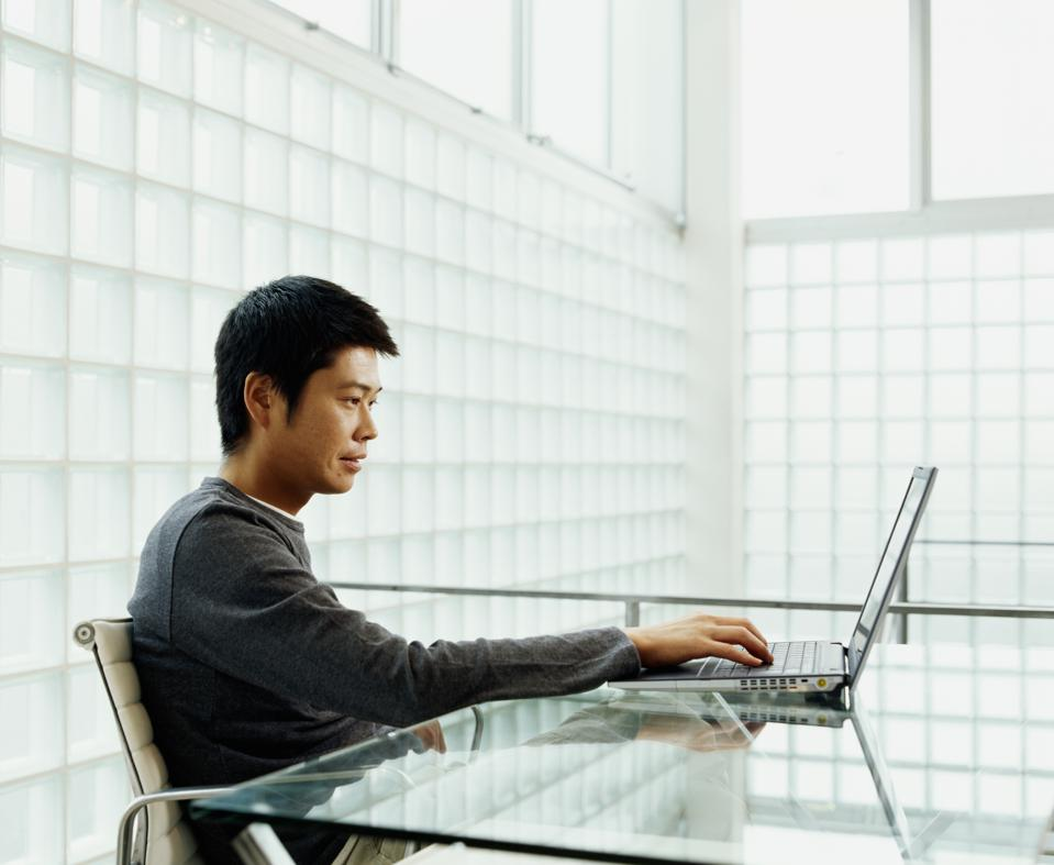 Young man using laptop at desk, side view