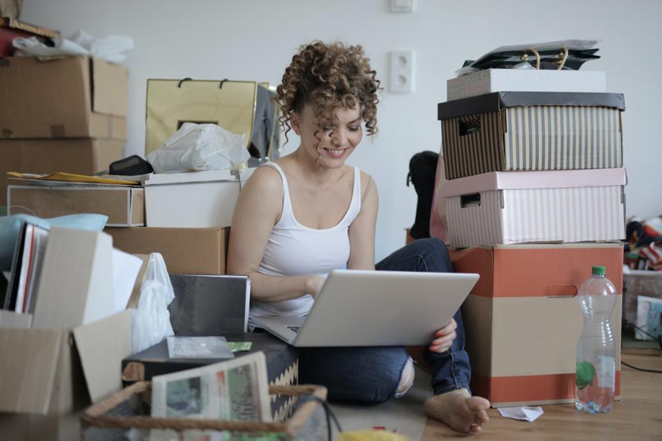 Customer shopping on laptop surrounded by boxes and purchases
