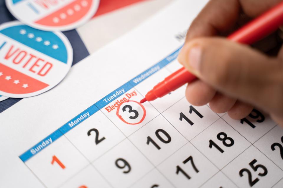 Close up of Hands marking november 3 election day on Calendar as reminder for voting - Concept of reminder for US election.