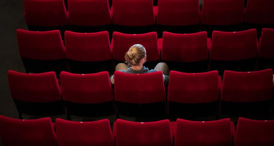 A woman sitting alone in a movie theater
