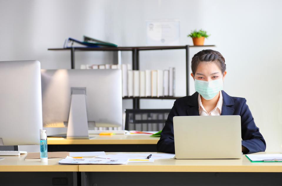 Female employee wearing medical face mask while working in the business office during covid-19 pandemic