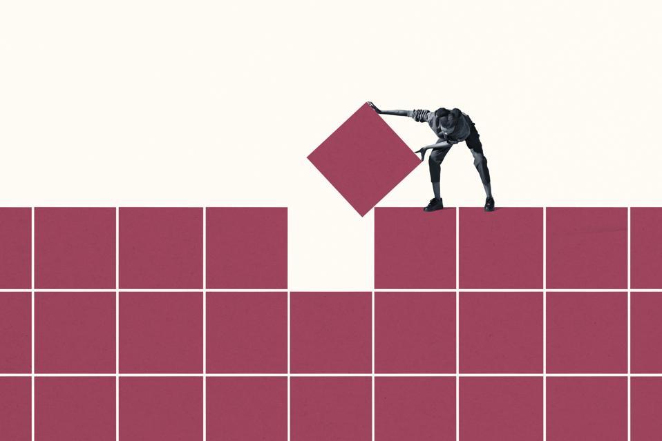 Woman positioning final magenta block in grid