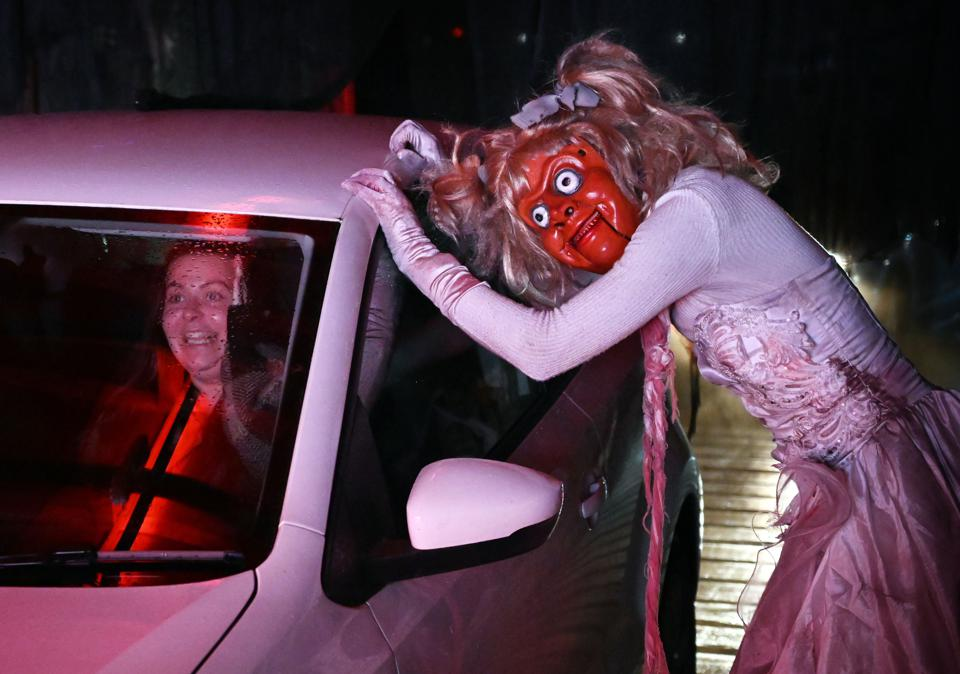An actor dressed as a character from a horror movie scares moviegoers at drive-in cinema
