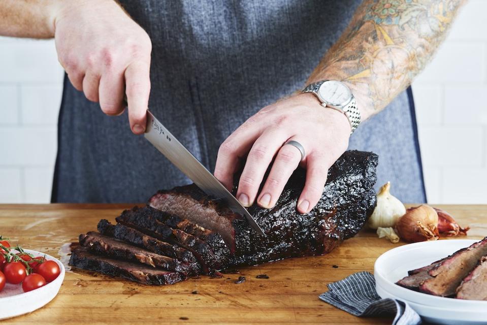 man cutting brisket