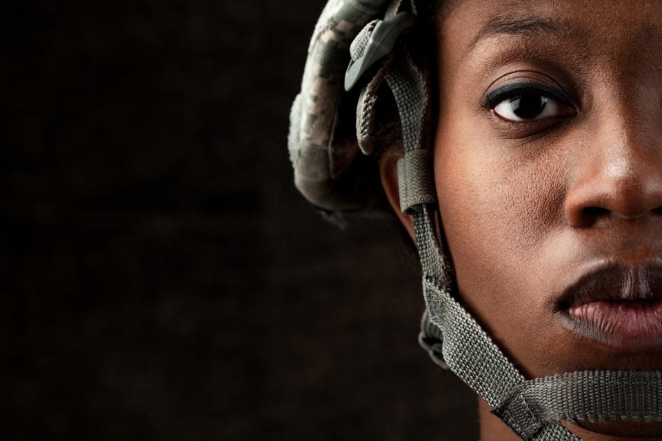 Black woman in an army helmet looking damn tough.