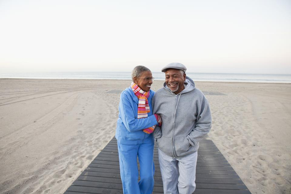 African American couple hugging and walking on beach