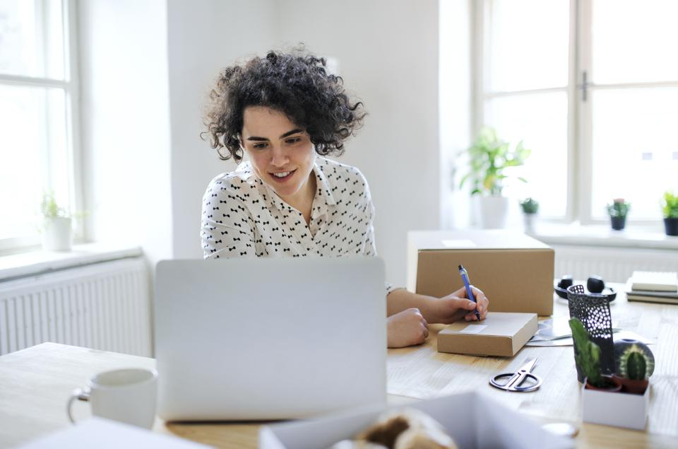 Smiling young woman preparing a package at desk