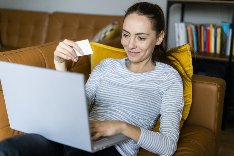 Young woman on couch at home shopping online