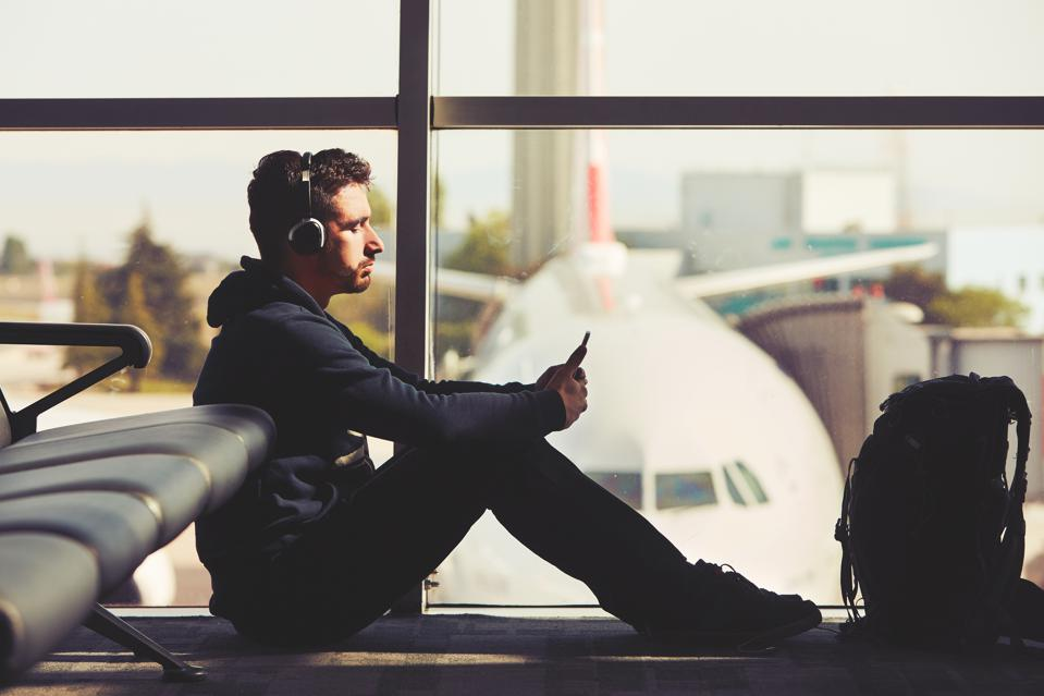Young traveler with headphones at airport