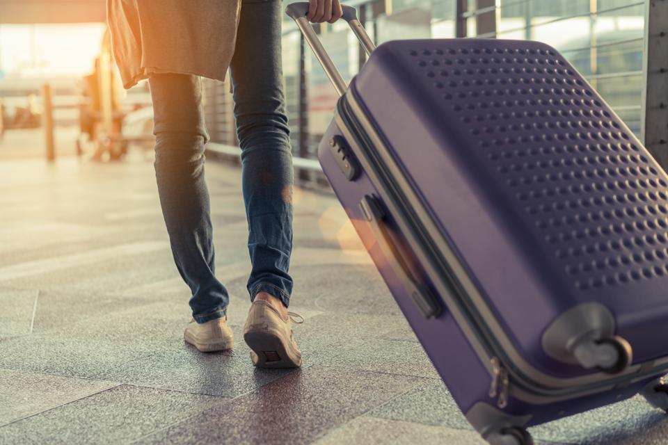 Young girl walking with luggage.