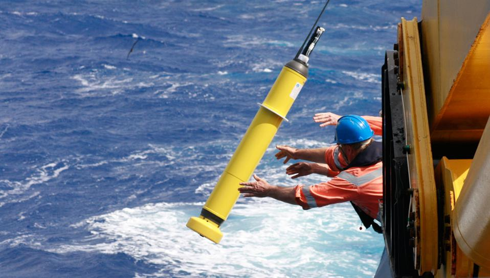 Scientists throw a yellow Argo Float robot into the water from a research vessel