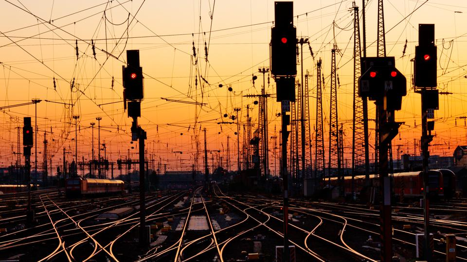 Intertwined railroad tracks with traffic lights at sunset