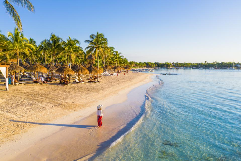 Woman walking caribbean beach Akumal Mexico tourism places you can travel right now