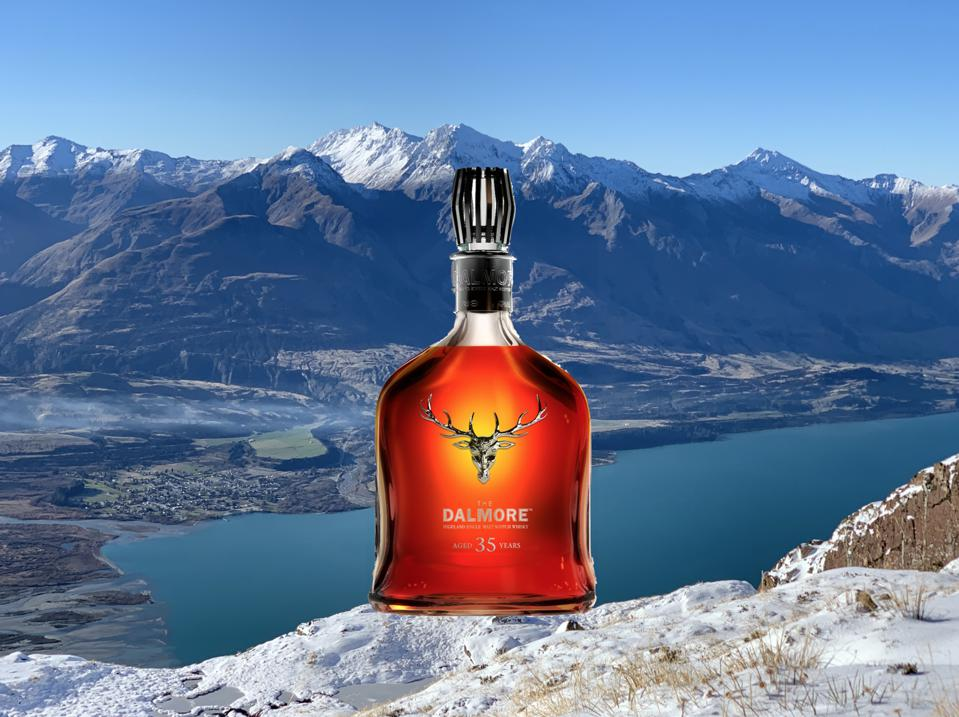 A brilliant orange-amber hued bottle sits among the snowcapped mountains of New Zealand