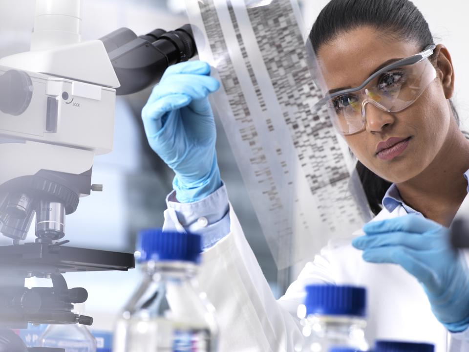 Scientist holding a data read-out from sequencing in a lab, wearing gloves and a lab coat.