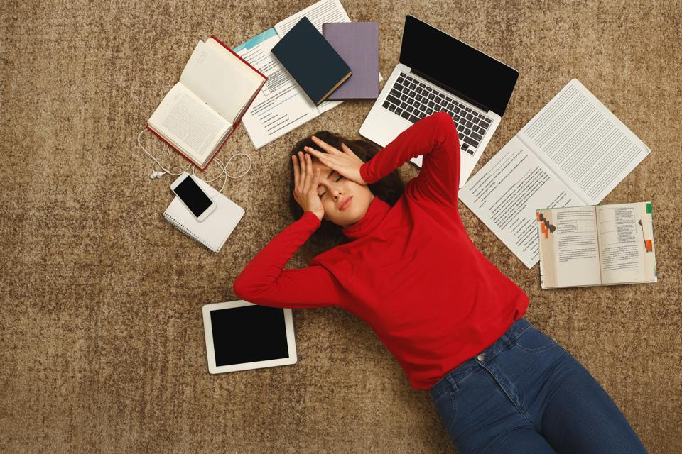Stressed out employee laying on the floor with devices and books showing high pressure and toxic work.