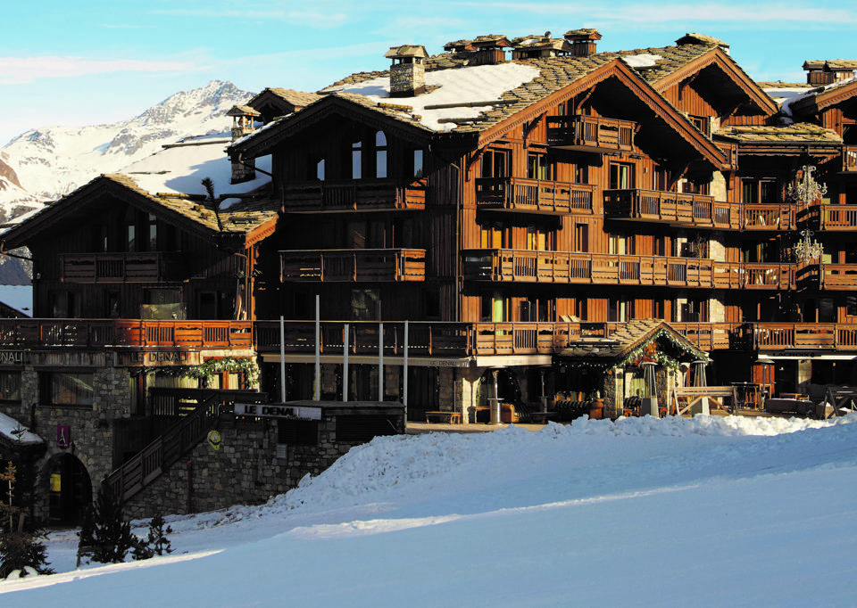 A large wooden chalet on the edge of a snow covered mountain